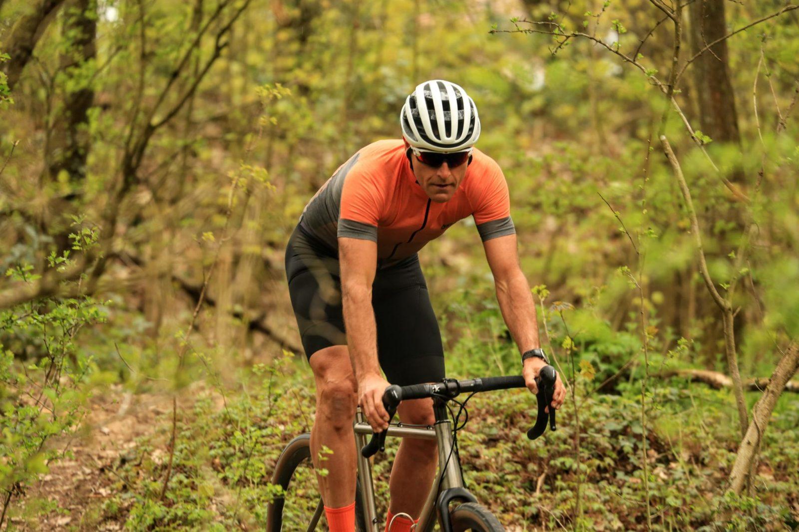 Cycliste gravel bois maillot gravel orange et gris