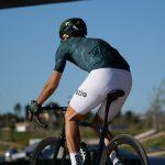 Cycliste vu de dos maillot vert cuissard blanc
