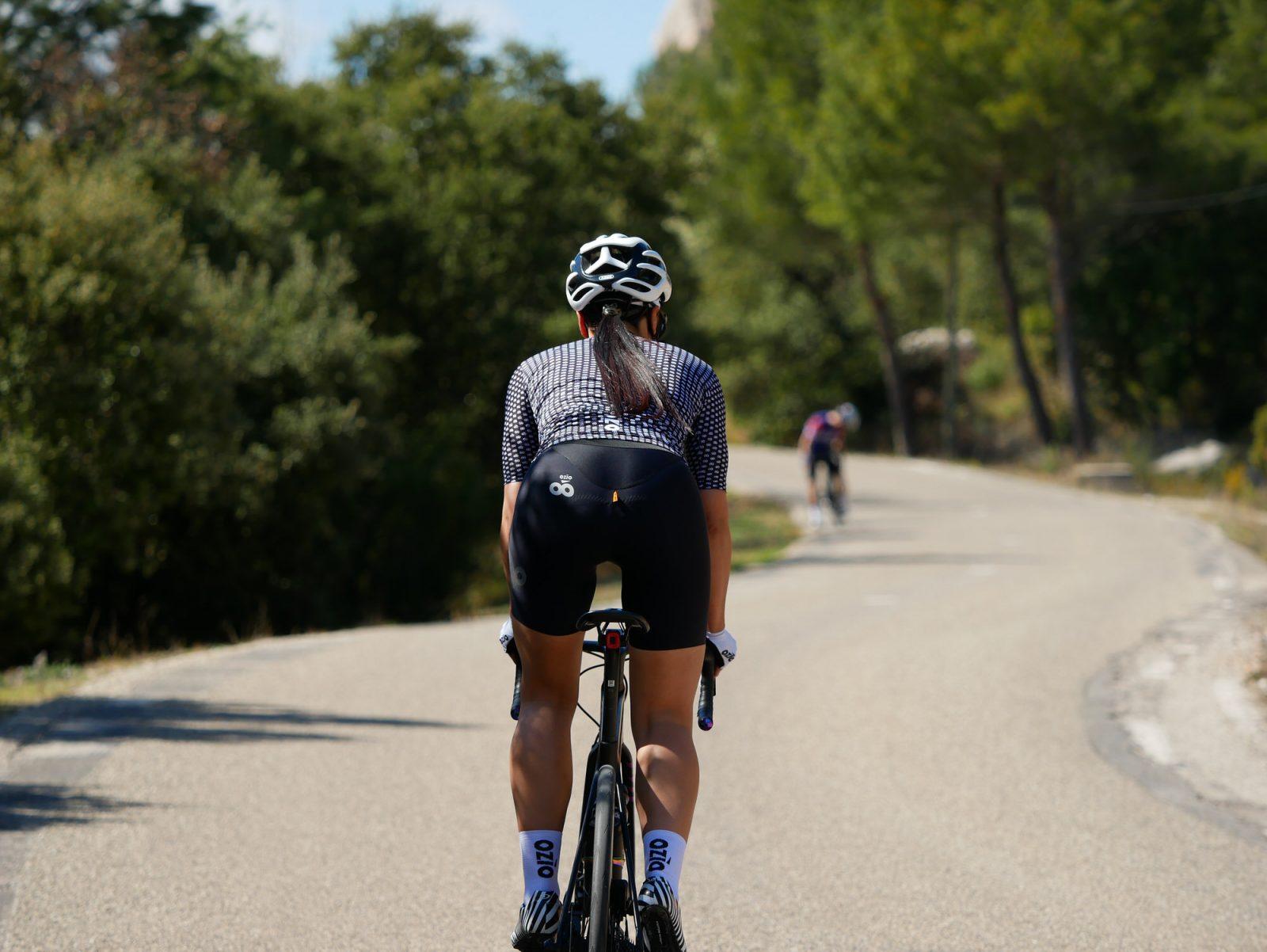 Vue de dos femme qui pédale maillot de vélo été femme et cuissard OZIO