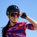 Femme cycliste regardant au loin avec lunettes de soleil, casquette et maillot de cycliste