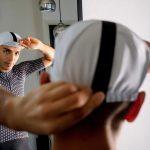 Homme regardant son reflet qui porte une casquette de vélo blanche et maillot de vélo