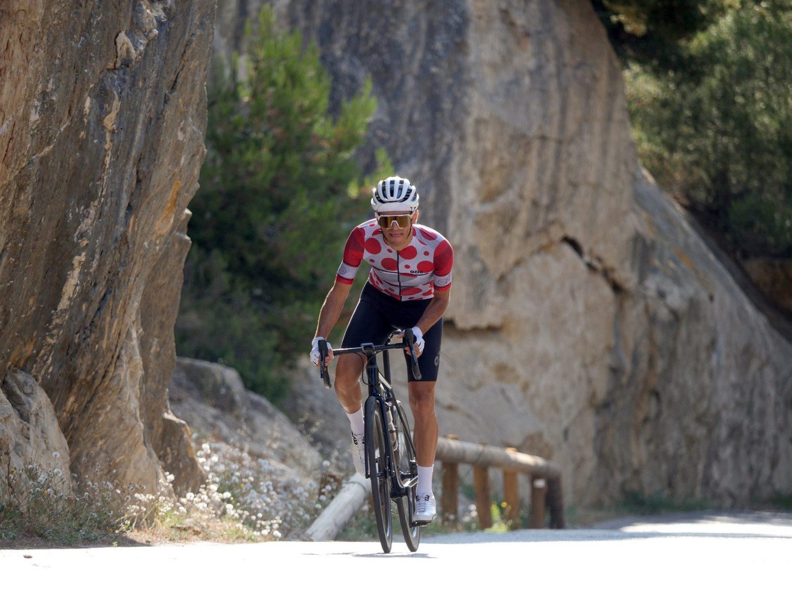 Maillot vélo blanc à pois rouge face cycliste en danseuse